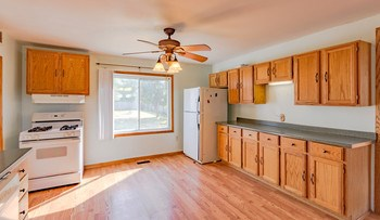 The large eat-in kitchen has laminate floors and a new fan plus tons of cabinet and counter space. (photo 3)