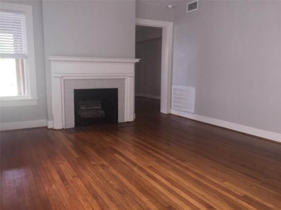 Living Room with mock fireplace and hardwood floors. The door leads to the dining room (photo 2)