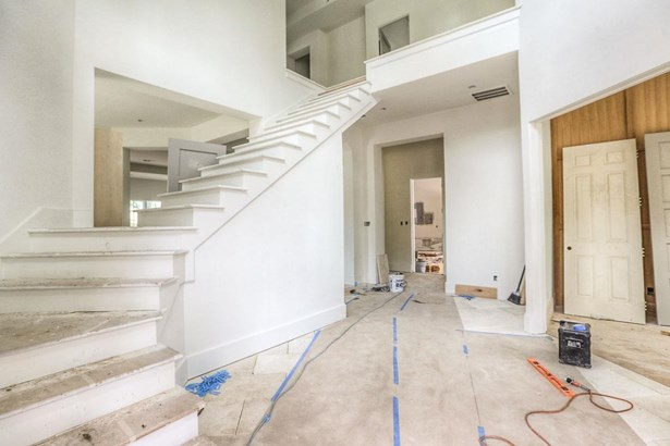 Through the 9 steel frame glass entry door guests are welcomed into the reception hall with winding staircase that will boast select white oak treads and custom designed baluster. Construction as of 7/10/17 (photo 2)