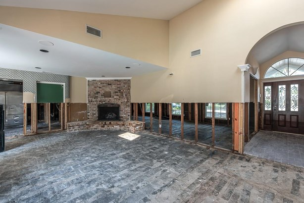 The large arched opening leads into the den with corner brick fireplace and hearth. (photo 5)