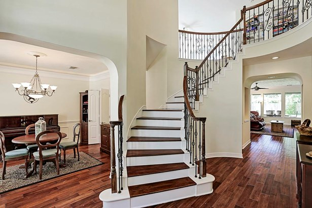 The grand entry features high ceilings and views of the stairs leading to the large game room and upstairs bedrooms. Upgraded wood flooring on the first floor provides warmth. (photo 2)
