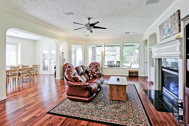 The large open family room can be seen from the kitchen and breakfast areas creating a wonderful open floor plan. Entry to the master suite is in the far right corner of this picture. (photo 5)