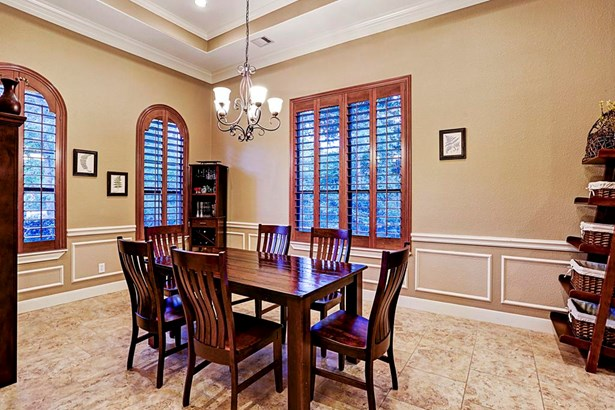 Alternate view of the dining room. This room contains custom crown moulding, stunning plantation shutters and a view of the front yard. (photo 5)