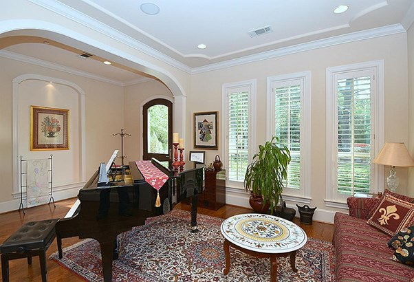 The 12x13 SF living room has wood floor, plantation shutters, and recessed lighting. (photo 4)