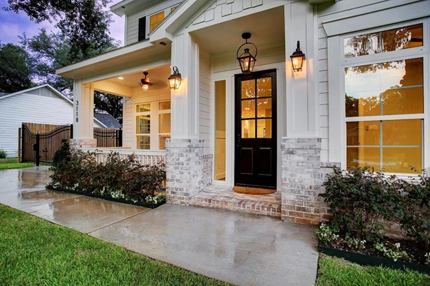 Inviting entry with copper gas lit carriage lantern over front door with two flanking carriage lights and covered porch (photo 3)