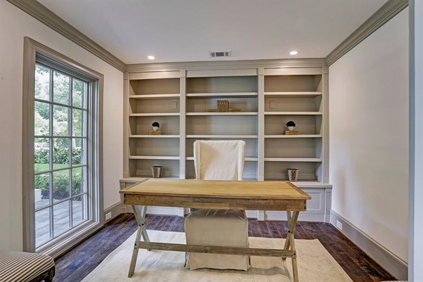 "To the left of the entry sits a stately study with a continuation of custom finished including impressive wood floors, site built display space, electrical outlets in the baseboards and 4"" recessed lighting highlights custom built-in bookshelves. (photo 4)"
