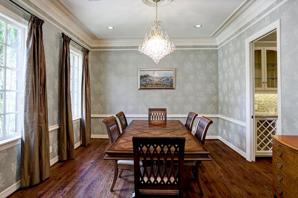 The spacious formal dining room is an entertainers dream! The room features crown molding and hardwood floors that flow right into the butlers pantry that is located on the right. (photo 4)