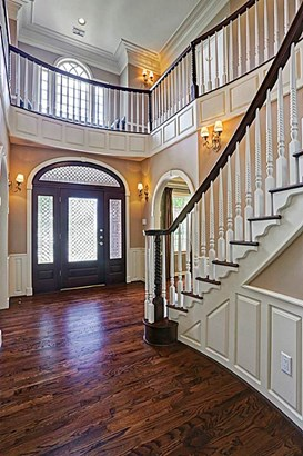 The foyer is impeccable. It features a beautiful double staircase with hardwood floors. (photo 5)