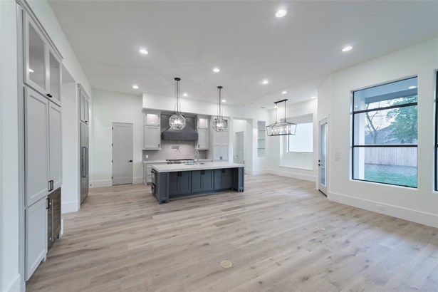 View of the kitchen from the family room. Entire first floor features wide plank oak floors in a light stain, twelve foot ceilings, large windows, and custom cabinetry. This room showcases additional back-lit glass cabinets, quartz counter tops, designer (photo 3)