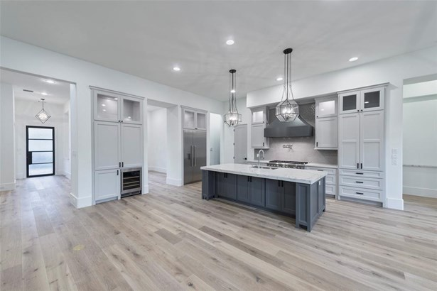 """Another view of this stunning kitchen shot with a view of the iron front door. This view really showcases the wide plank floors, ample storage including an """"appliance garage"""" in the kitchen to hide all of those kitchen necessities, large double door refri (photo 4)"""