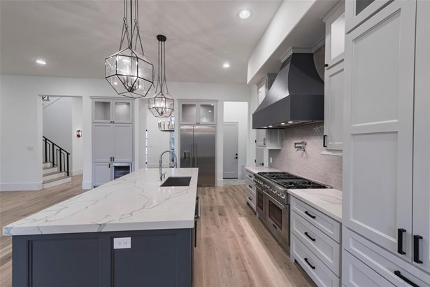 Kitchen features beautiful custom cabinetry and designer light fixtures. Gorgeous veined quartz counters and mosaic tile backsplash make the kitchen feel luxurious. Situated in the center of the home just off of the mudroom/garage and with wonderful flow (photo 5)