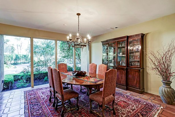 Dining room boasts an iron chandelier and large windows, flooding the space with tons of natural light. Thoughtfully placed windows through out the home showcase multiple views of the lush outdoor landscaping and manicured grounds. (photo 3)