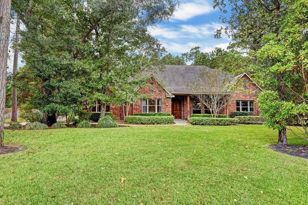 This home is composed of a beautiful brick and wood exterior. The lush green shrubbery makes the home feel private while allowing for easy maintenance. Upon entry you are greeted by a welcoming lighted covered front porch perfect. (photo 3)
