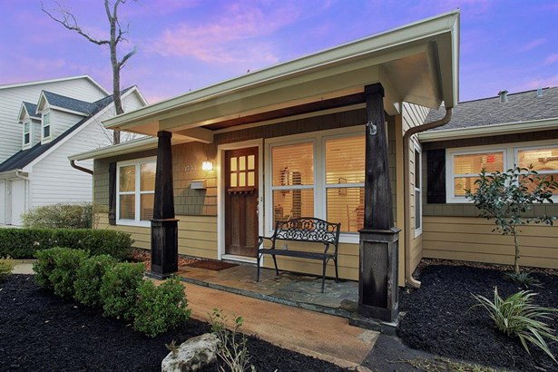 Charming front porch sits between wood columns. (photo 3)