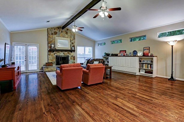 Huge family room with high ceilings and decorative beam leads out to backyard through double doors. Hardwood floors are carried throughout home and well placed windows let plenty of light into the home. Wood burning fireplace with stone surround is the fo (photo 4)