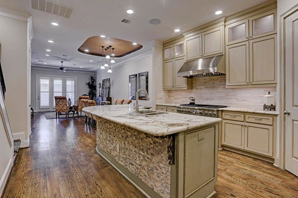 Stacked stone was added to the base of the large island. Cabinets extend to the ceiling with glass inserts in many providing tons of storage. (photo 5)