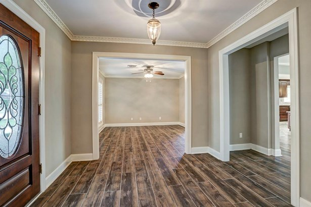 The living areas have wood look ceramic tile, plantation shutters and crown molding. (photo 5)