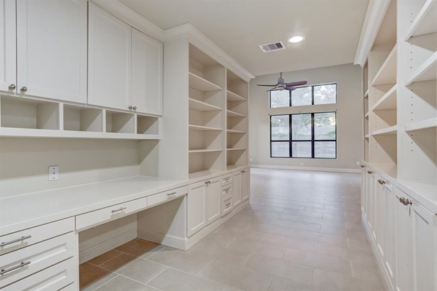 Front formal areas are separated from the den and kitchen by a walk through library area with built in knee space. Adjustable shelving lends itself to easy decorating and display space. (photo 5)