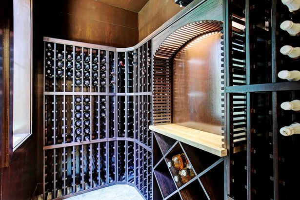 The chilled wine room is located behind the glass wrought iron door. The wine rack offer different size storage shelves and a lighted display area. (photo 4)
