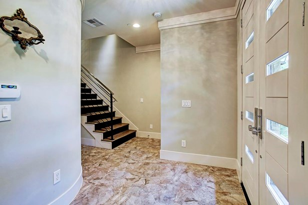 The foyer has neutral paint tones, tile flooring with darker brown tones that blend in with the wood on the stairs, crown molding and is pre-wired for an alarm system. You also have access to the 2-car garage from the foyer. (photo 5)