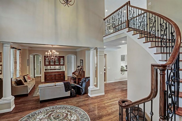 The spiral staircase with wrought iron balusters looks toward a living room that can convert to a formal dining room. (photo 5)