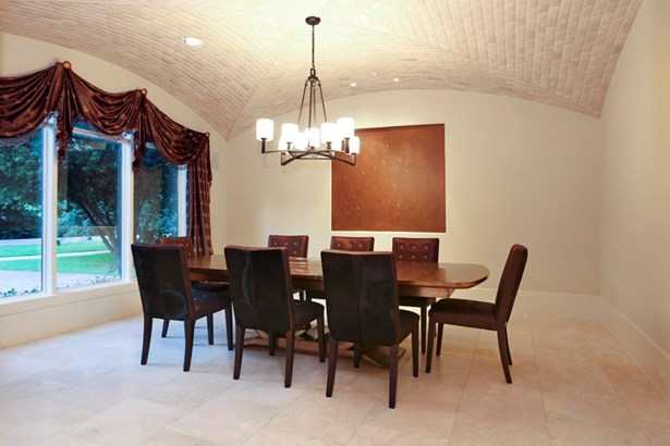Barrel stone ceiling and travertine floors enhance the formal dining room with abundant light coming in through the tall triple windows and a view to the front lawn. (photo 4)