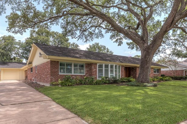 A side angle view of the home with mostly brick exterior and nextled under a beautiful mature shade tree with lush green lawn and landscaping. (photo 2)