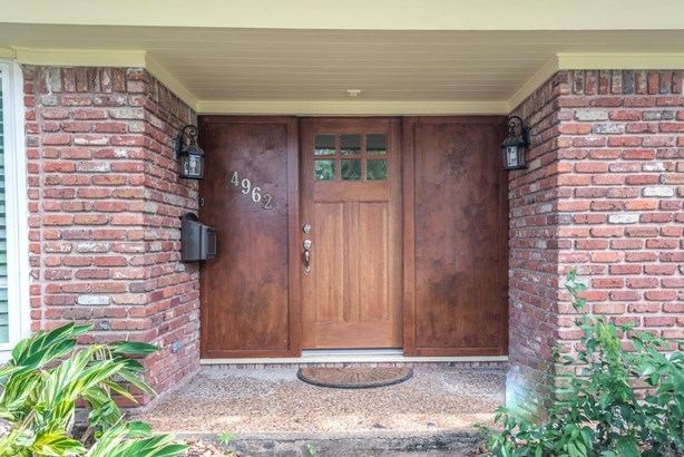 Covered front entrance with wood door and side lanterns welcomes your arriving guests. (photo 3)