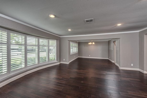 Wow! This beautiful space is the formal living and dining room area with gorgeous wood floors, accent crown molding and custom shutters on the large curved wall of windows. (photo 5)