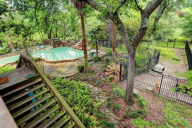 There is a large double dog run with a high end aluminum fence that wraps the wooded area behind the pool. Note that all the stone has been cleaned since this photo was taken. The stairs to the left are going up to the deck off the kitchen and den. (photo 5)