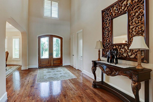 Two story foyer features double hardwood door with leaded glass and hardwood floor. To the left (right in this photo) is a coat closet and half bath. (photo 5)