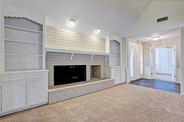 Open den with vaulted ceiling has expansive wood burning fireplace with hearth and is flanked by built-ins. (photo 4)