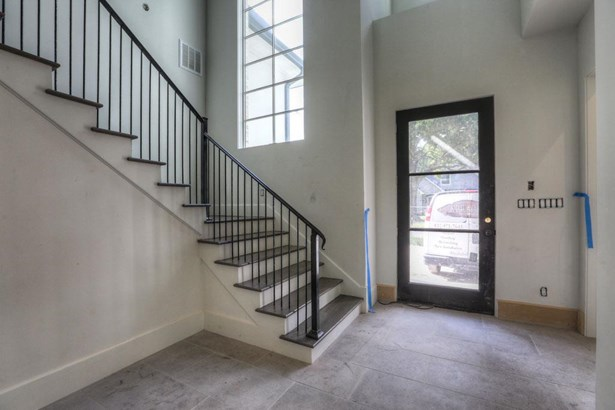Enter into the welcoming foyer through the 9 steel frame glass door. Features include 22 ft ceilings and custom designed wrought iron balustrade adorning the squared staircase with Select White Oak treads. (photo 2)