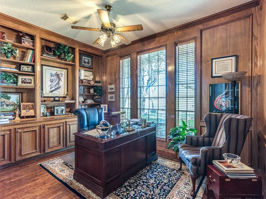 Great executive study offers paneled walls, hardwood flooring, tall windows for natural light, and built-in cabinetry and upper shelving to meet your office needs. (photo 4)