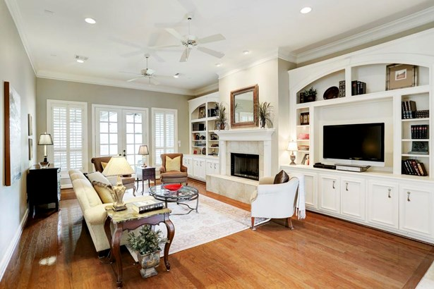Family room (20x15) with wall of built ins, lower cabinetry, crown molding, gas fireplace with tile surround, hardwood flooring, recessed lighting and French doors to covered outside patio/yard space. North south exposure with indirect sunlight. (photo 2)
