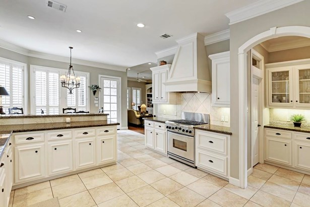 Kitchen is (15x12) very roomy with abundant storage and counter space. Elegant millwork, arched butler s pantry with glass front cabinets. Granite countertops, tumbled tile backsplash, and stainless appliances. This home shows very well. (photo 5)
