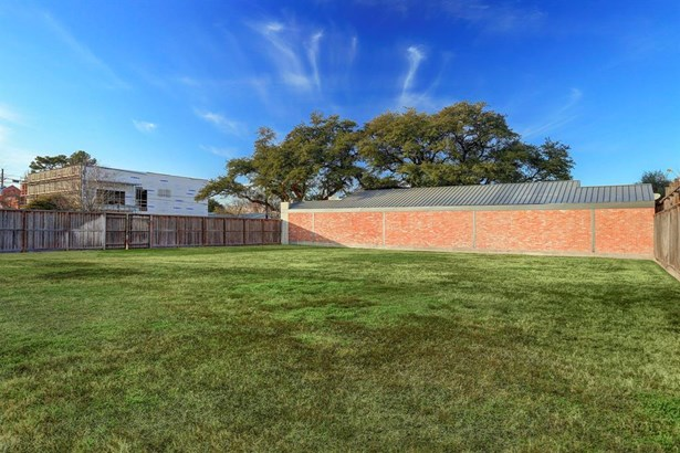Approximately 11000 sf of land is fenced and cleared. Brick wall shown is side view of the building located on the Property. New Construction in left view is across Joanel street. (photo 2)
