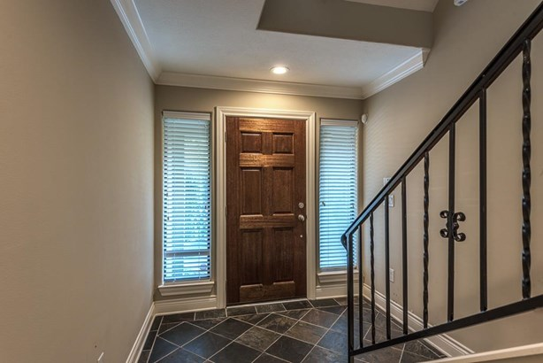 Slate front entry with crown molding leads to a downstairs bedroom and bath. The iron and wood stairs leads to the 2nd floor living spaces. (photo 4)