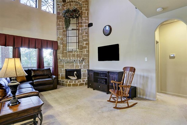 Gorgeous views, a two story stone fire place, and custom iron work in the upper windows make this family room so very special. (photo 4)