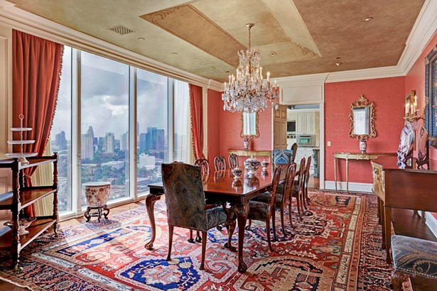 The grand dining room- accessed through the kitchen & den, can be completely privatized with a collapsing dividing wall. Fine views indulge occupants while the custom paint detailing & well placed low voltage throughout captivate the senses inside. (photo 3)