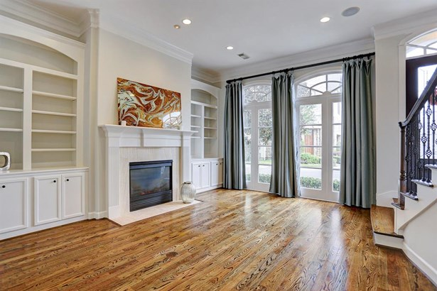 View of the formal living room featuring a beautiful fire place mantle and custom built-ins on both sides (photo 5)