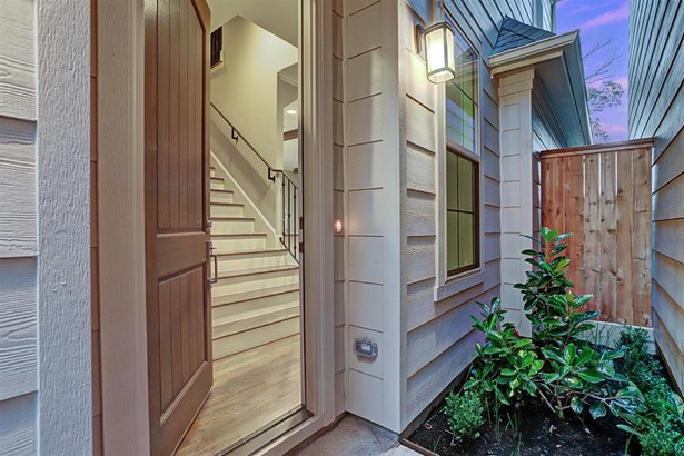 Solid wood entry door with sturdy chrome hardware opens to the first floor living. Front door is flanked with exterior coach lighting. Photo of a similar completed home in the community. (photo 4)