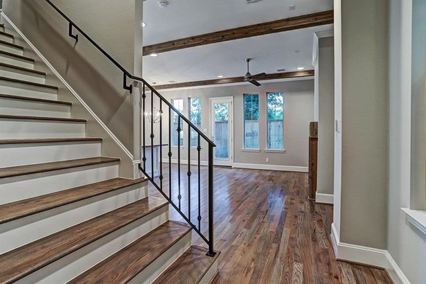 View of entryway and foyer with solid wood door and solid wrought iron staircase with simplistic spindles. Photo of a similar completed home in the community. (photo 5)