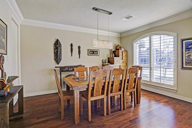 The 11x14 SF formal dining room has custom hanging lamp, hardwood floor and plantation shutters. (photo 4)