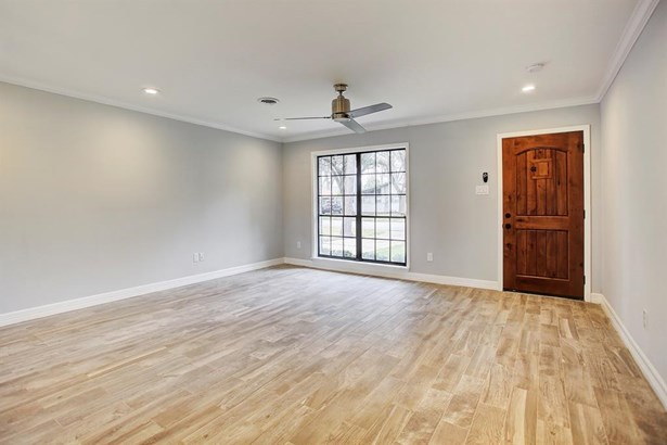 The open floor plan feels organic. Streams of light enter the home through the many windows. On the floor is woodgrain ceramic tile. The walls have been freshly insulated, sheetrock-ed, and painted. Crown molding was added for that crowning touch. (photo 4)