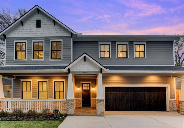A craftsman style exterior is accented by gray body paint, white trim color and brick accents. Traditional craftsman door compliments the wooden garage door. (photo 1)