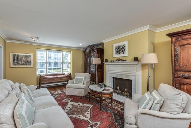 Formal living room with fireplace, wood floors & crown molding overlooks the front lawn (photo 2)