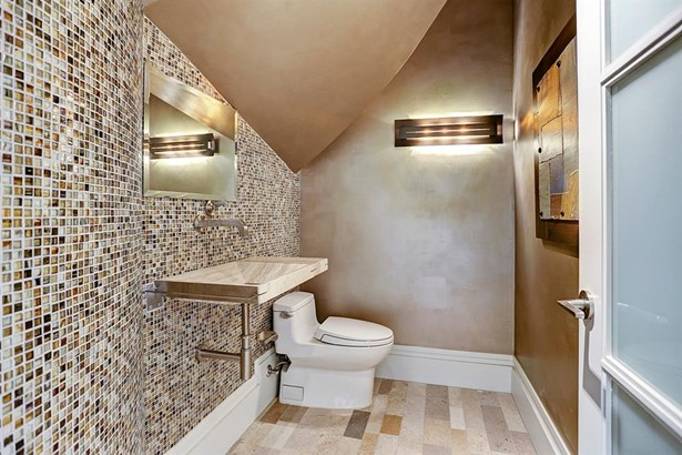 Downstairs half bathroom found underneath the staircase. The mirror has the electronic ability to provide light. (photo 2)