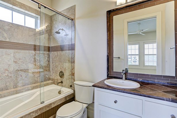 Ensuite upstairs secondary guest bedroom full bathroom with shower, comfortable bath tub, tiled counter tops and gorgeous granite. (photo 4)