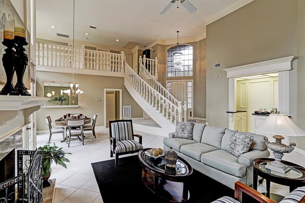 Inviting two story entrance features an elegant floating staircase, wet bar and tile floors. (photo 3)